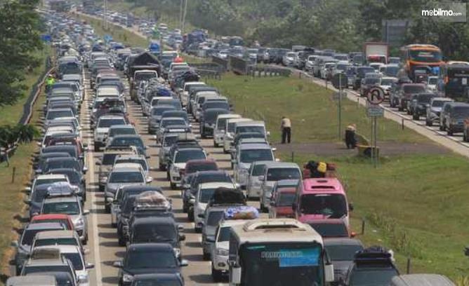 Gambar ini menunjukkan banyak mobil berdesakan di jalan tol saat musim mudik