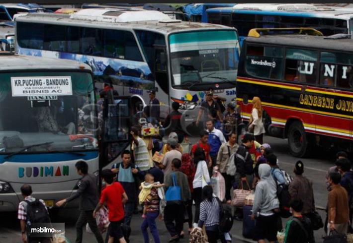 Gambar ini menunjukkan banyak orang sedang berada di terminal bus