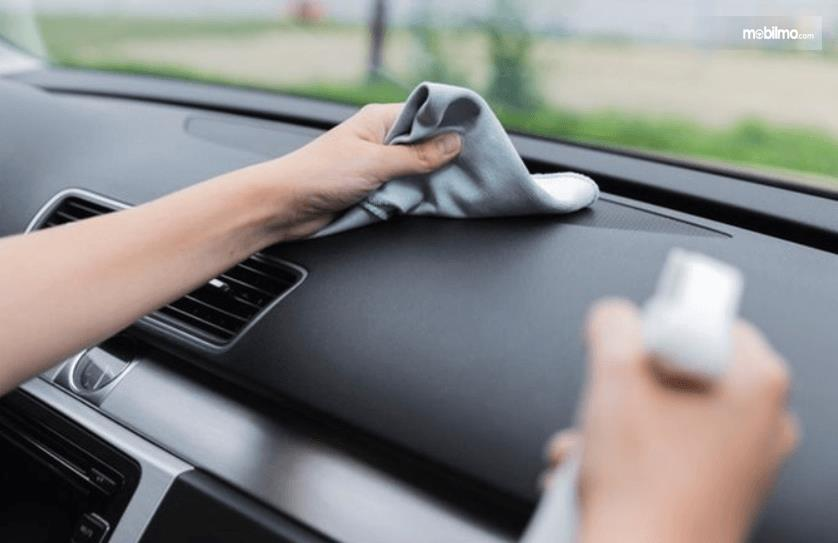 Gambar ini menunjukkan sebuah tangan mengelap dashboard mobil