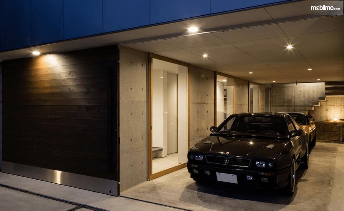 Gambar ini menunjukkan sebuah mobil berada di garasi mobil
