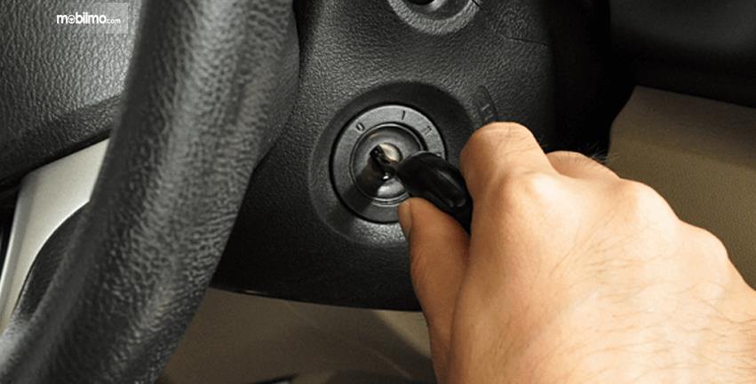 Gambar ini menunjukkan sebuah tangan memutar kunci mobil