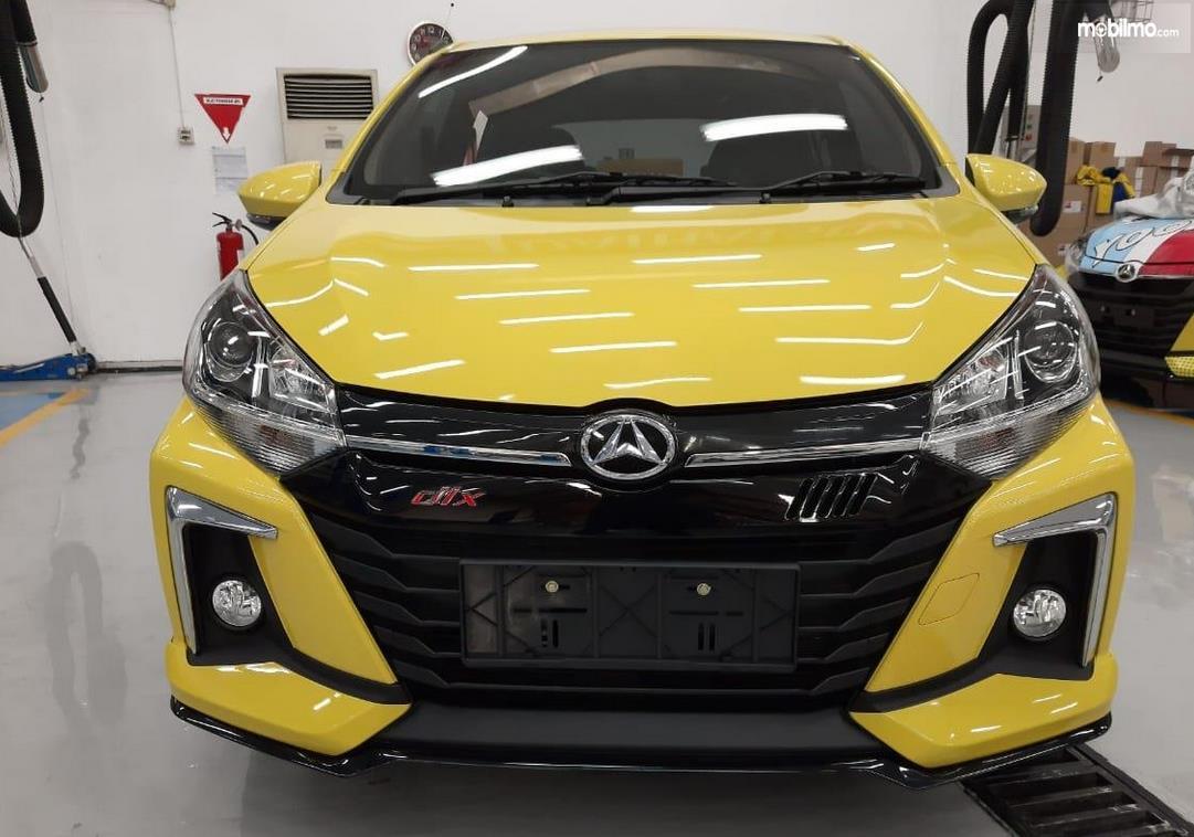 Gambar ini menunjukkan mobil Daihatsu New Ayla kuning tampak depan