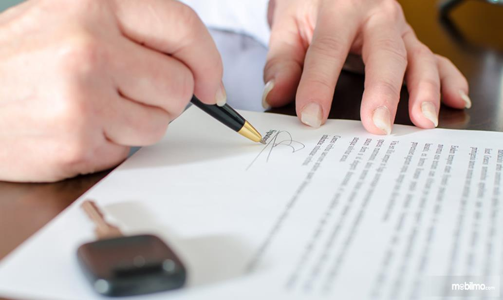 Gambar ini menunjukkan 2 tangan  satu pegang bolpen menandatangani