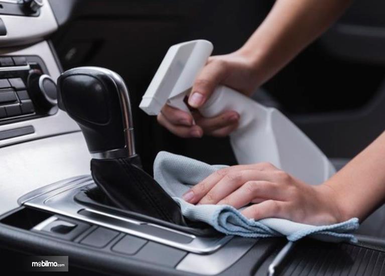 Gambar ini menunjukkan sebuah tangan membersihkan tuas transmisi