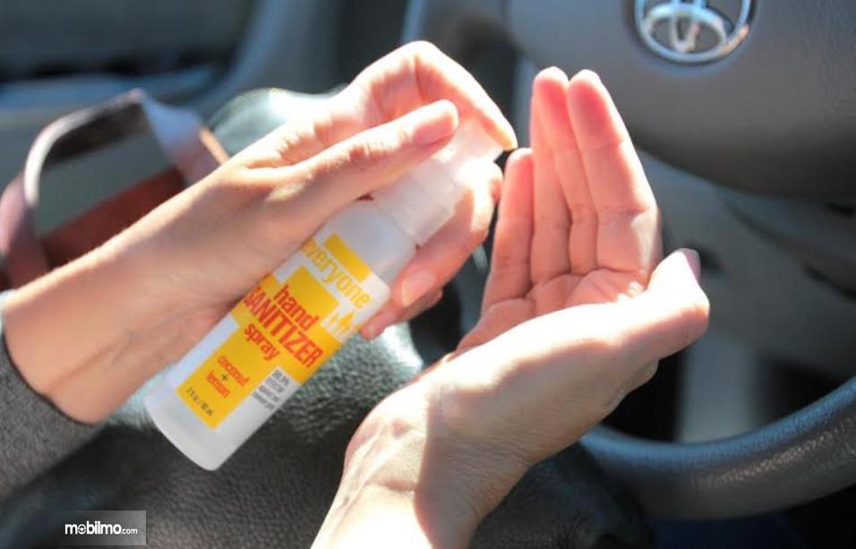 00Gambar ini menunjukkan penggunaan hand sanitizer dalam mobil