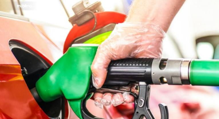 Gambar ini menunjukkan sebuah tangan memegang alat untuk mengisi bahan bakar
