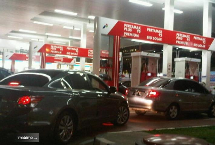 Gambar ini menunjukkan beberapa mobil sedang melakukan pengisian bahan bakar di malam hari