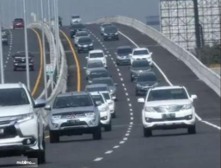 Gambar ini menunjukkan beberapa mobil sedang melaju tampak bagian depan