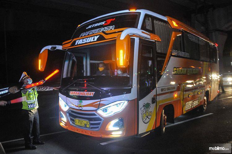 Foto menunjukkan seorang petugas menghalau bus yang membawa pemudik untuk balik ke Jakarta