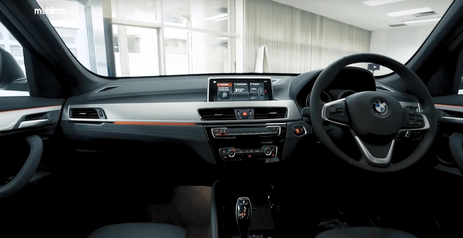 Gambar ini menunjukkan dashboard dan kemudi mobil BMW X1 sDrive18i xLine 2020