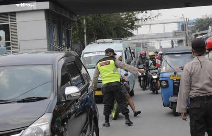 Gambar ini menunjukkan seorang polisi menghentikan pengendara sepeda motor untuk diperiksa