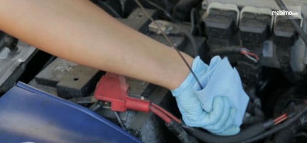 Gambar ini menunjukkan sebuah tangan bersihkan dipstick oli