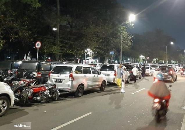Gambar ini menunjukkan banyak mobil dan sepeda motor di pinggir jalan