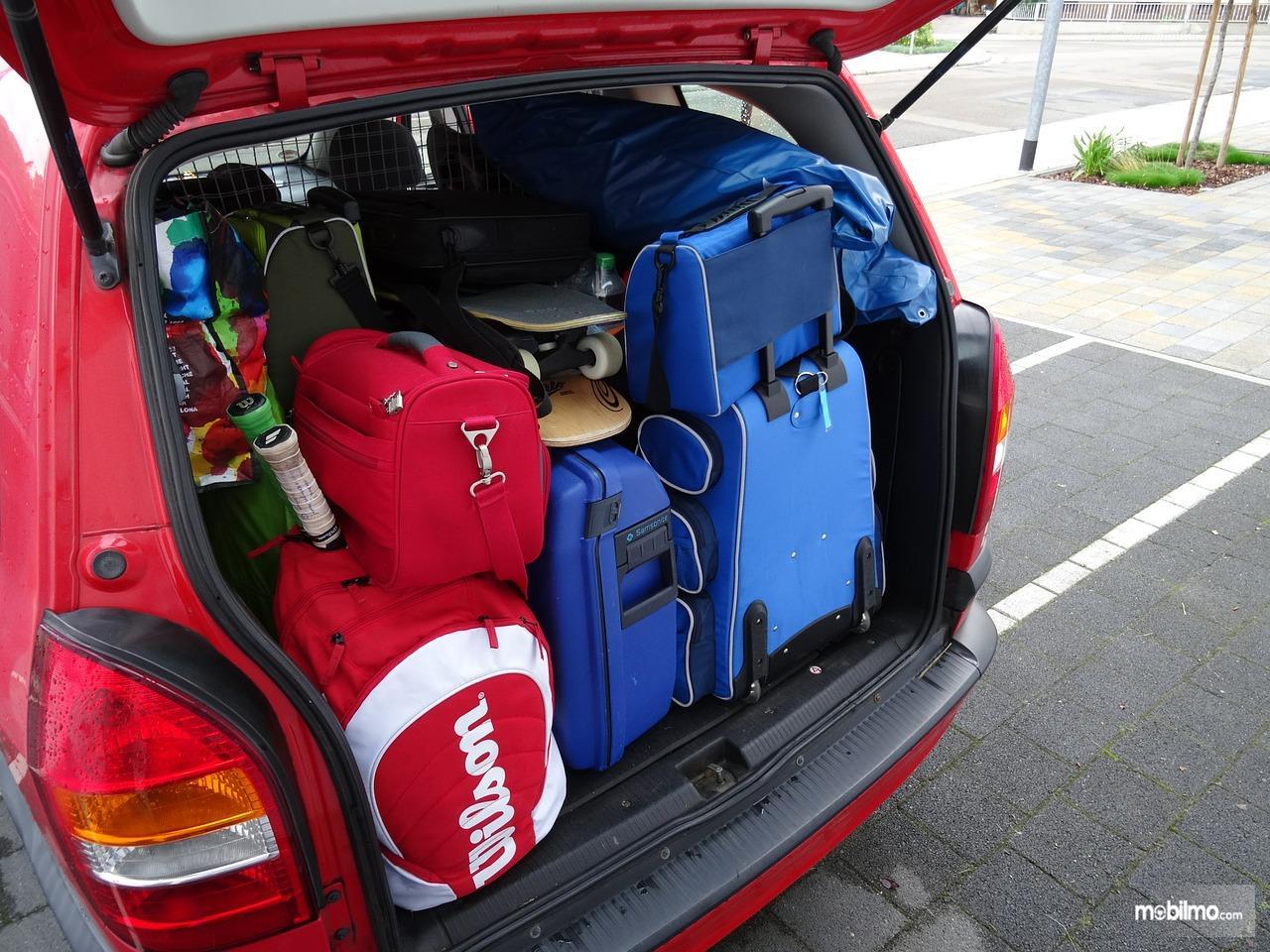 Foto menata barang di bagasi mobil