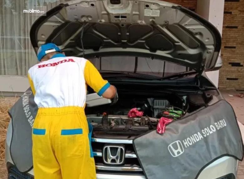 gambar ini menunjukkan seorang mekanik Honda sedang memperbaiki mesin mobil