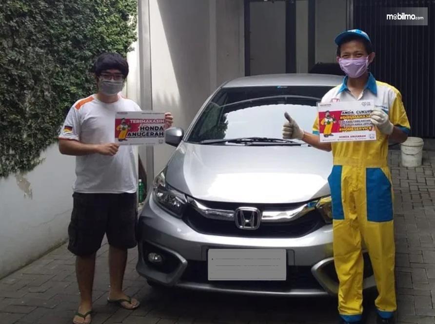 Gambar ini menunjukkan 2 orang berdiri di depan mobil Honda dengan pegang sesuatu