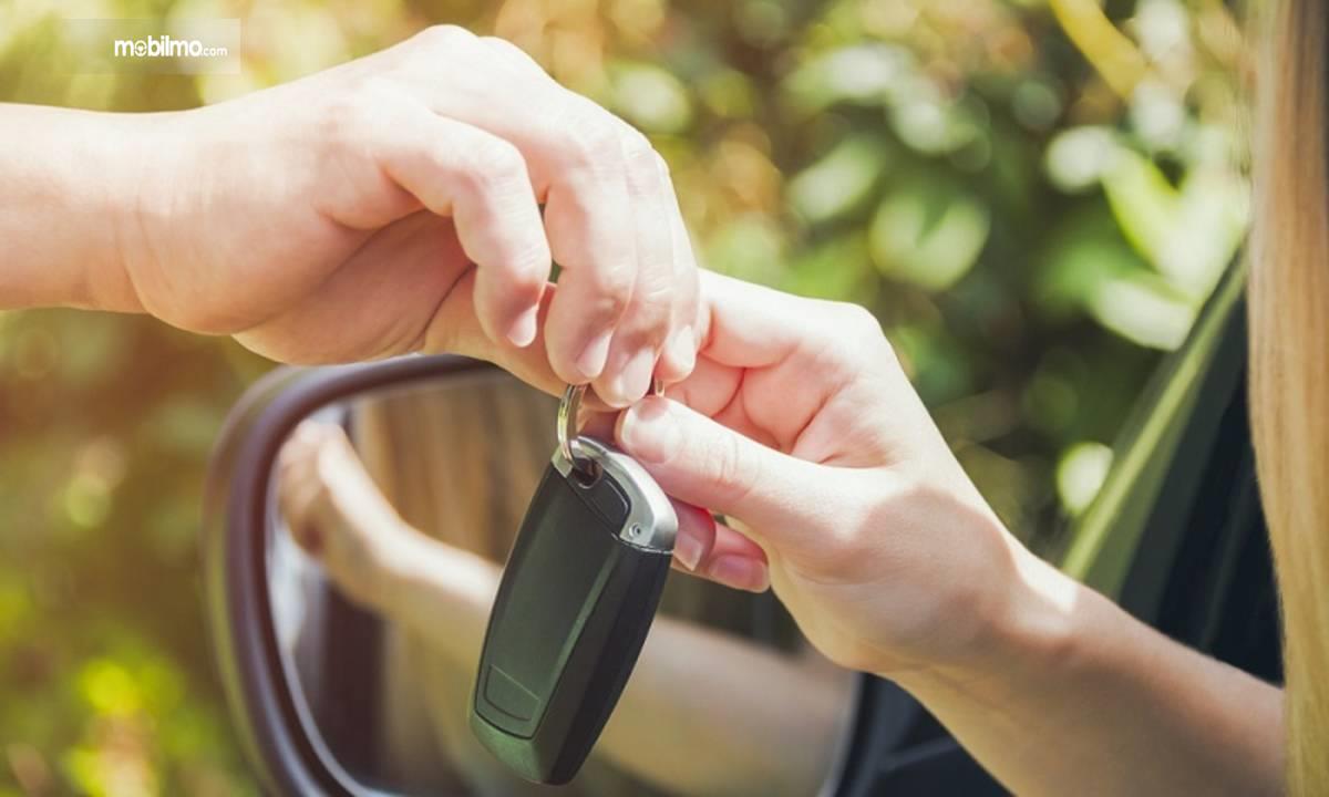 Foto menunjukkan serah terima kunci mobil