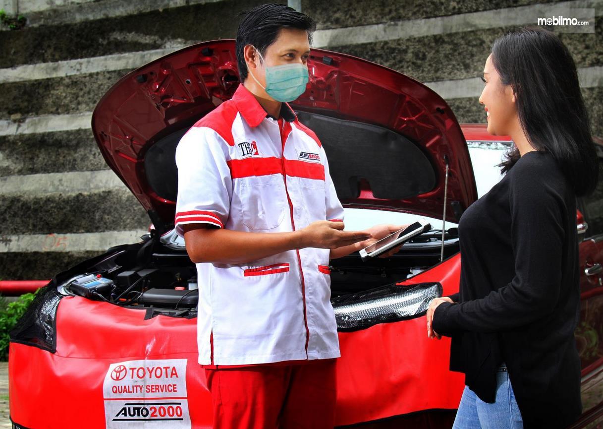 Gambar ini menunjukkan seorang mekanik sedang berdiri di depan perempuan untuk servis mobil