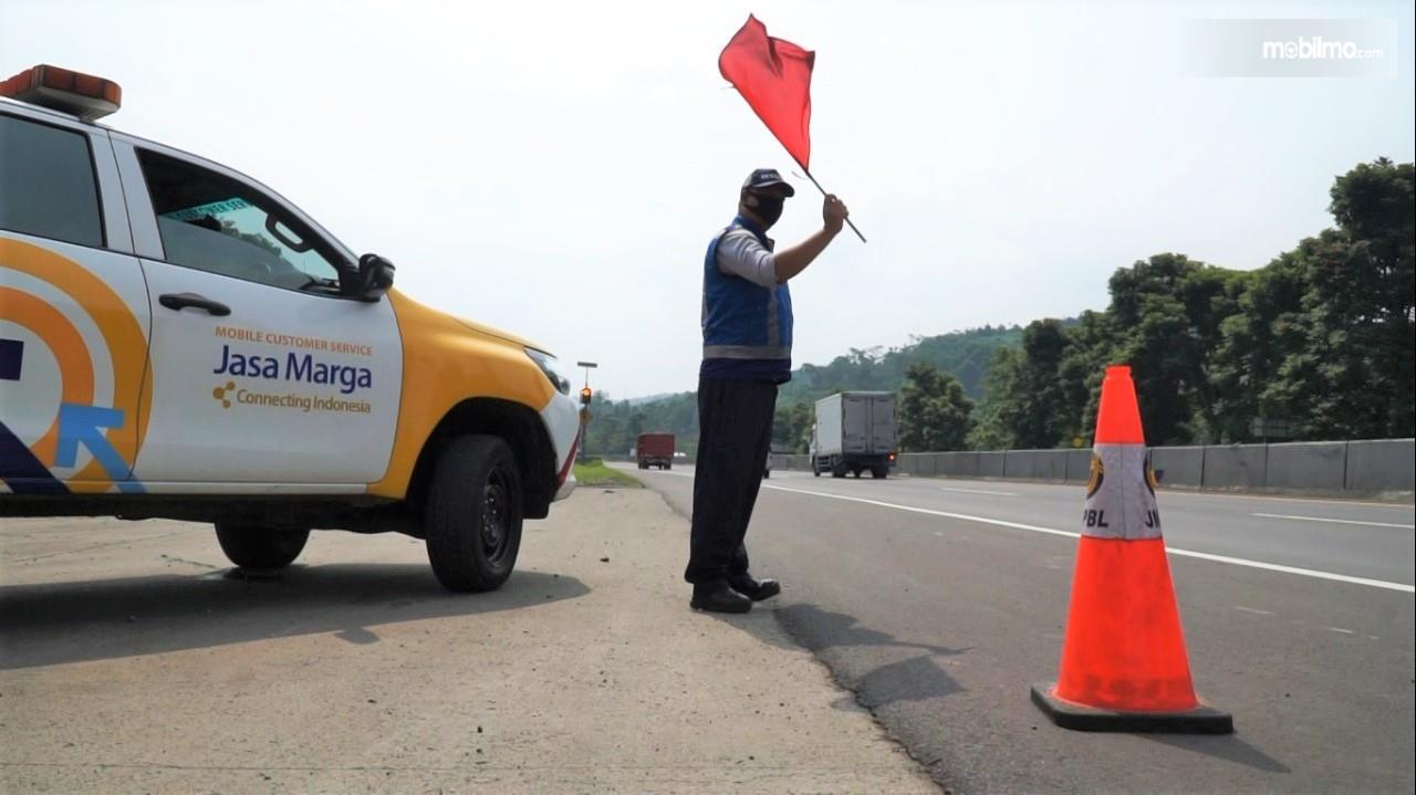 Foto menunjukkan petugas jalan tol