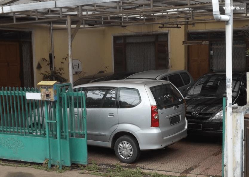 Gambar ini menunjukkan beberapa mobil berada di garasi depan rumah