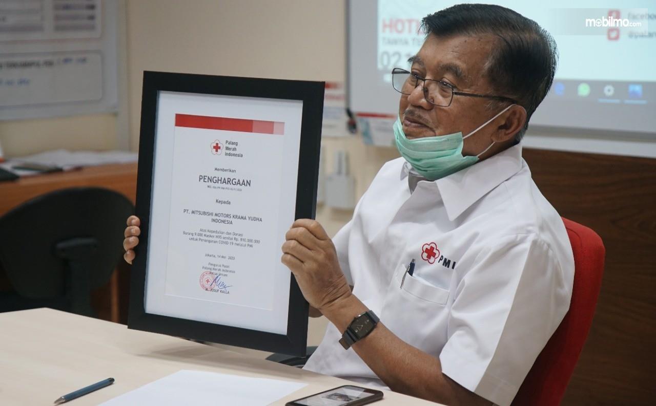 Foto menunjukkan Ketua PMI, M. Jusuf Kalla menunjukkan piagam bantuan dari Mitsubishi