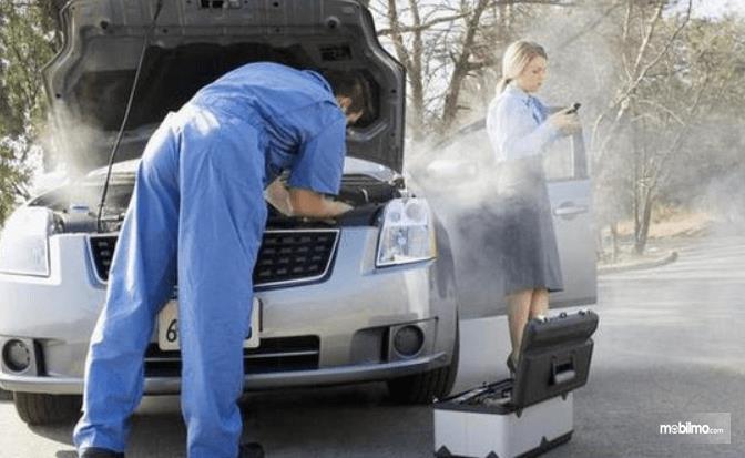 Gambar ini menunjukkan seorang mekanik dan wanita di dekat mobil berasap
