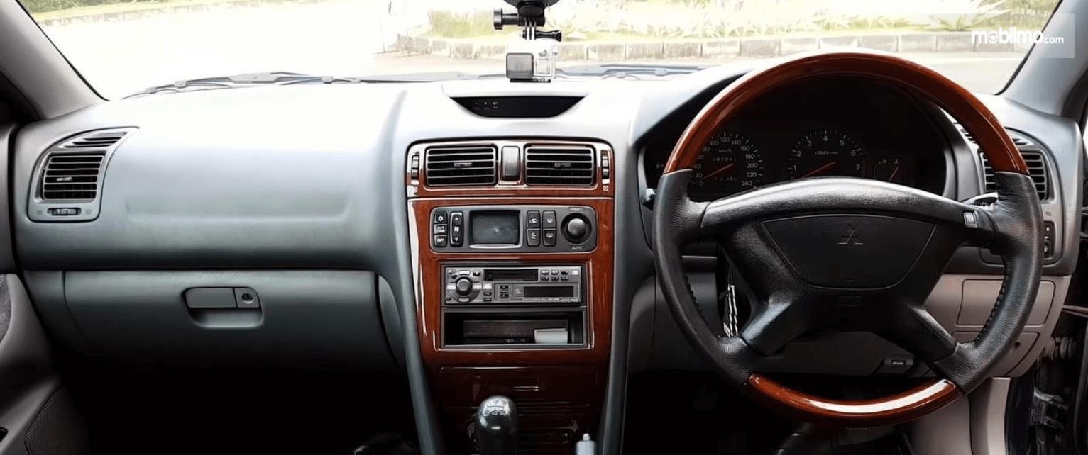 Gambar ini menunjukkan dashboard dan kemudi mobil Mitsubishi Galant 1998
