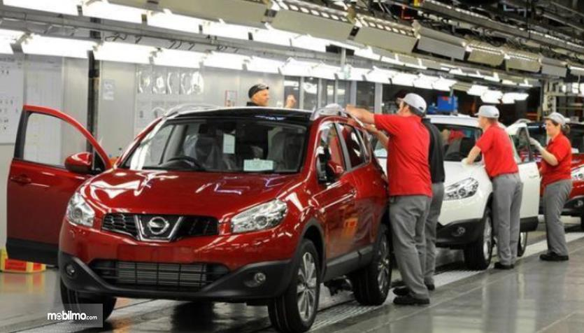 Gambar ini menunjukkan produksi mobil merah dengan banyak orang pakai baju merah