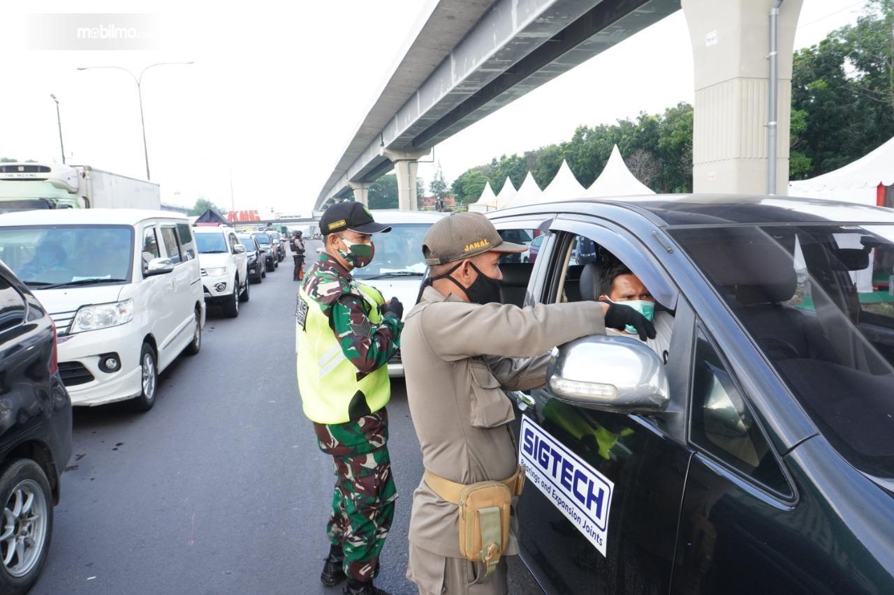 Foto menunjukkan petugas dari Jasa Marga memeriksa pengendara di jalan tol