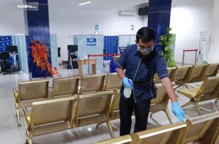 Gambar ini menunjukkan seorang pria sedang menyemprot kursi