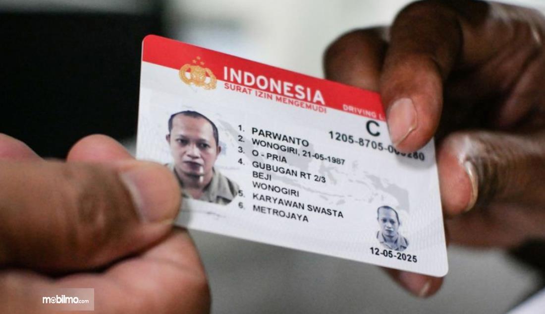Gambar ini menunjukkan 2 buah tangan sedang memegang SIM