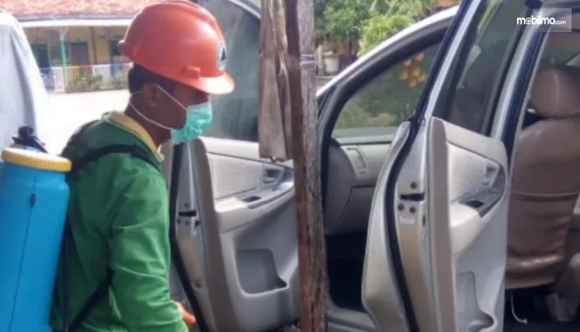 Gambar ini menunjukkan seorang pria menyemprot kabin mobil dengan desinfektan