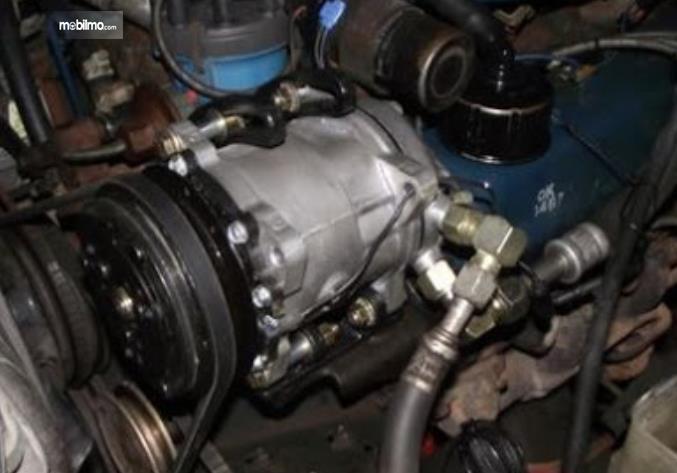 Gambar ini menunjukkan kompresor AC mobil yang terdapat pada bagian mesin mobil