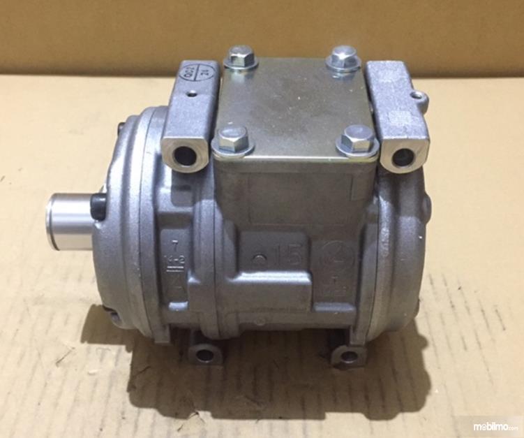 Gambar ini menunjukkan kompresor AC mobil kondisi baru