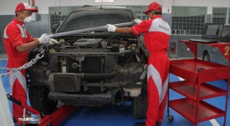 Gambar ini menunjukkan 2 mekanik mobil sedang memperbaiki mobil