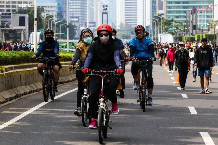 Foto menunjukkan aktivitas bersepeda tetap memakai masker