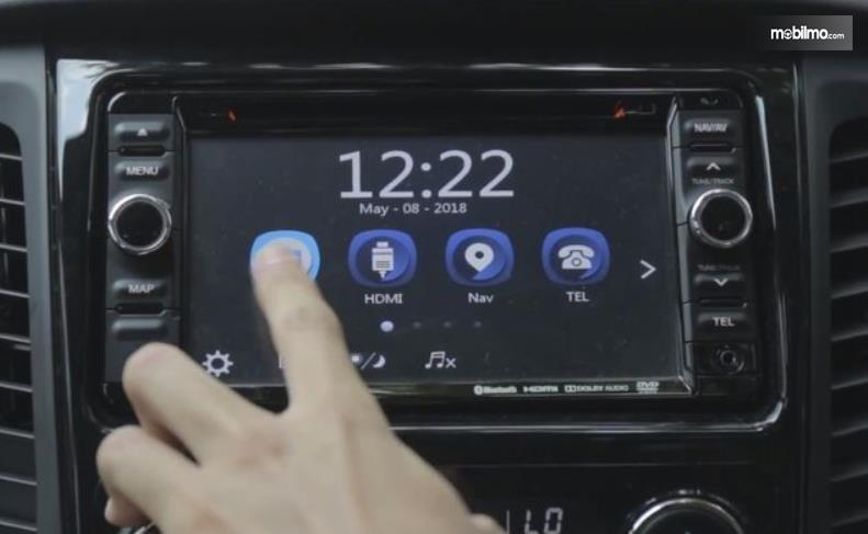 Gambar ini menunjukkan sebuah jari menekan layar head unit