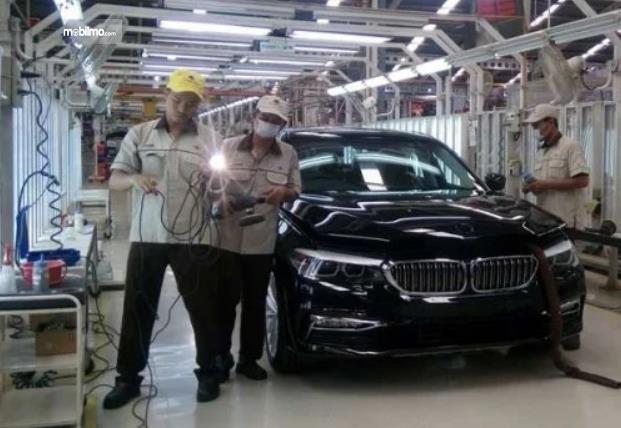 Gambar ini menunjukkan 3 karyawan dan 1 buah mobil BMW