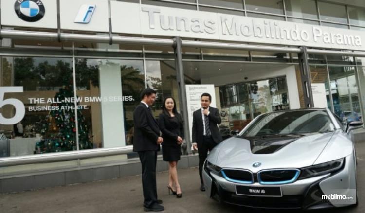 Gambar ini menunjukkan 3 orang dan satu buah BMW i5