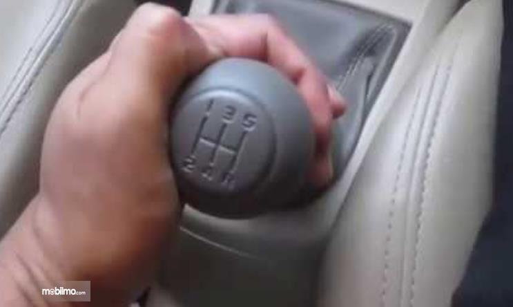 Gambar ini menunjukkan sebuah tangan memegang tuas perseneling mobil manual