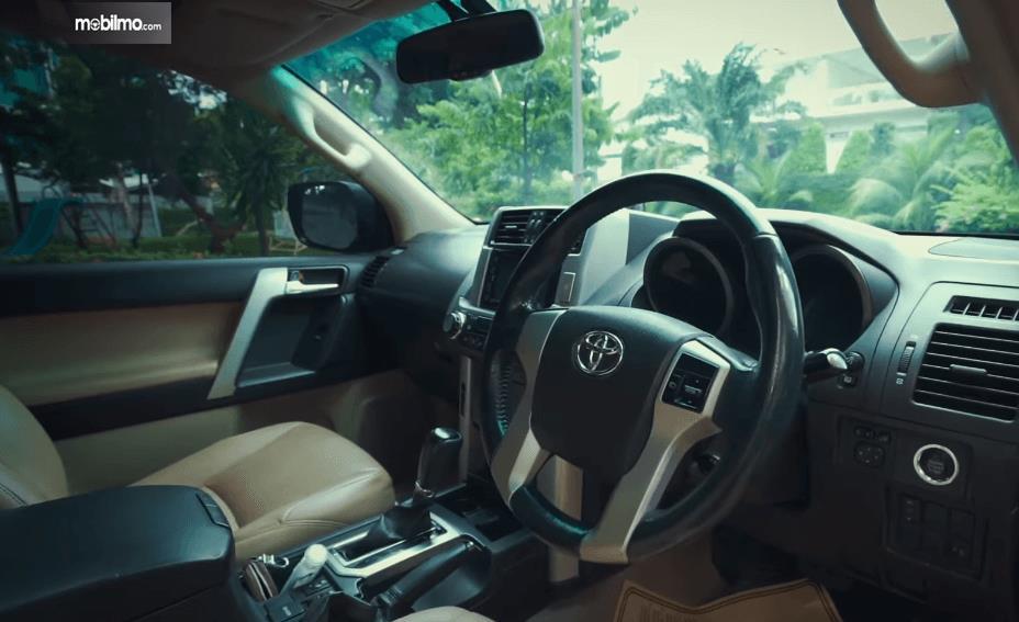 Gambar ini menunjukkan dashboard dan kemudi mobil Toyota Land Cruiser Prado J150 2010