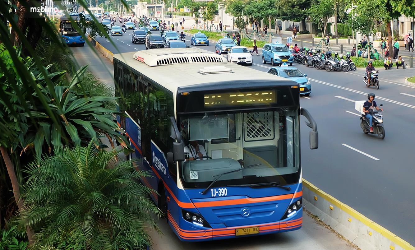 Gambar ini menunjukkan bus Transjakarta melaju di jalurnya