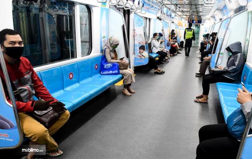 Gambar ini menunjukkan beberapa penumpang Transjakarta pakai masker dengan diberi jarak antar penumpang