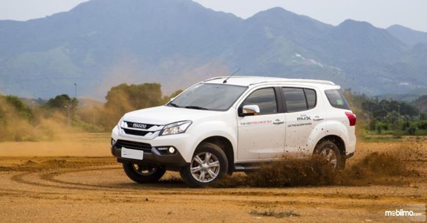 Gambar ini menunjukkan mobil Toyota Fortuner putih tampak samping