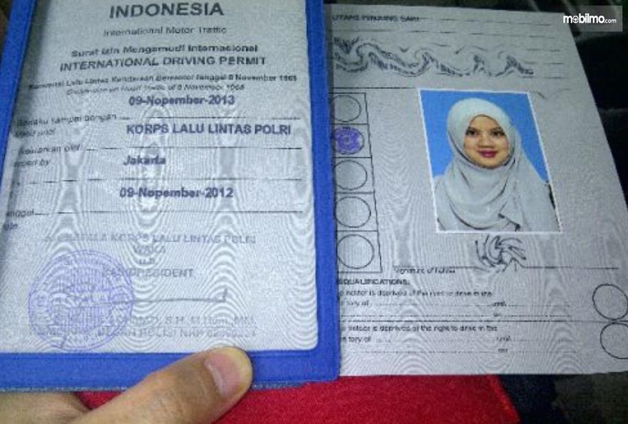 Gambar ini menunjukkan SIM Internasional dengan warna putih dan foto background biru