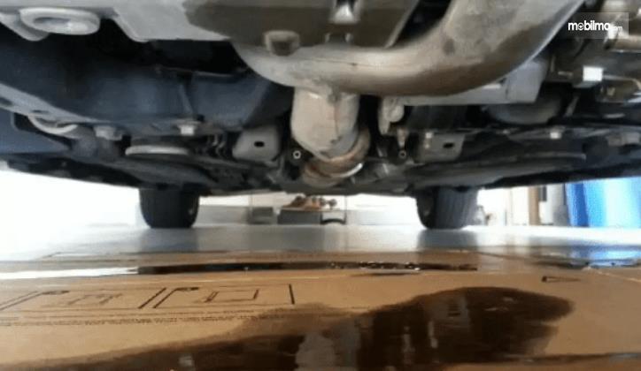 Gambar ini menunjukkan oli di lantai dan bagian kolong mobil