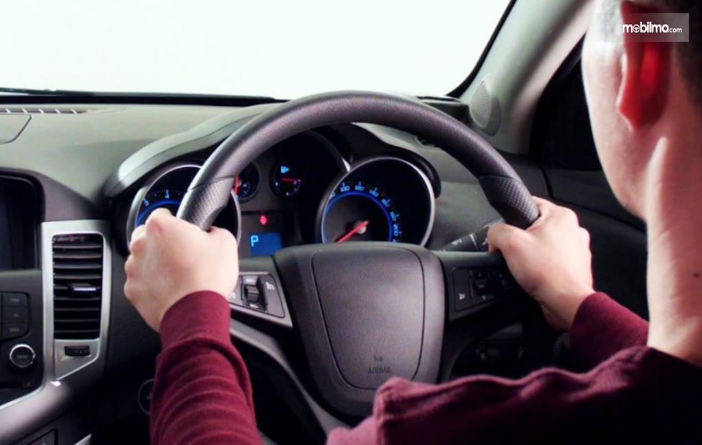 Gambar ini menunjukkan seorang pengendara memegang kemudi mobil
