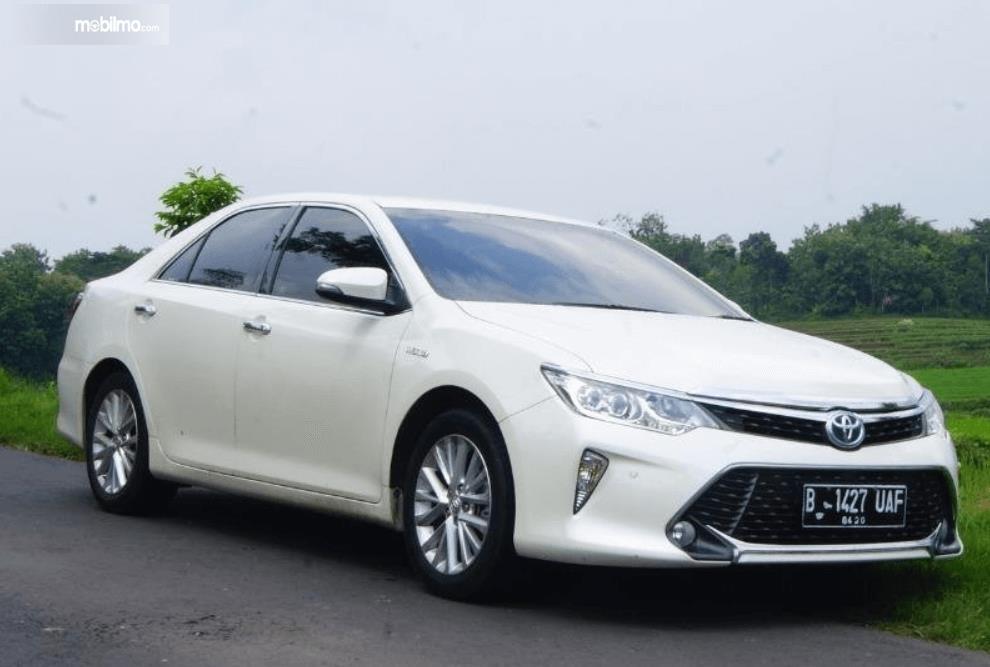 Gambar ini menunjukkan bagian samping mobil Toyota Camry 2.5 Hybrid 2015 putih