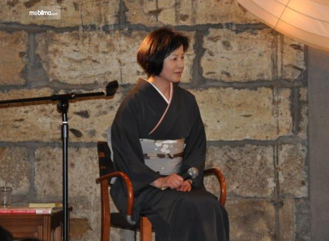 Gambar ini menunjukkan Kyoko Shimada sedang duduk