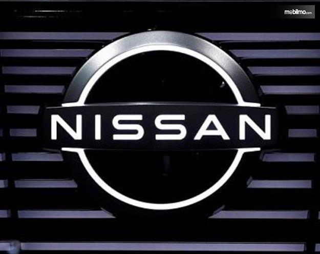 Gambar ini menunjukkan tulisan dan logo Nissan pada mobil